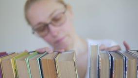 De vrouw met glazen in de bibliotheek zoekt onder de boeken op het boekenrek stock footage