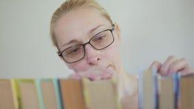 De vrouw met glazen in de bibliotheek zoekt onder de boeken op het boekenrek stock videobeelden