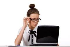 De vrouw met glazen zit bij een lijst en het werken Stock Afbeelding