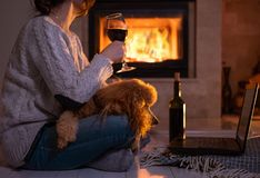 De vrouw met haar hond zit bij de de vloer en het drinken wijn stock foto