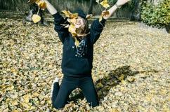 De vrouw met de herfst verlaat en daling ter beschikking gele esdoorngeep royalty-vrije stock afbeelding