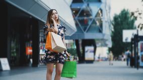 De vrouw met het winkelen zakken geeft opdracht tot taxi dichtbij een Winkelcentrum stock videobeelden