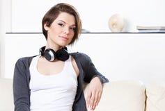 De vrouw met hoofdtelefoons gaat aan muziek luisteren Stock Afbeeldingen