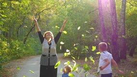 De vrouw met kinderen werpt op de bladeren stock footage