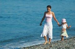 De vrouw met klein meisje gaat op kust Royalty-vrije Stock Afbeeldingen