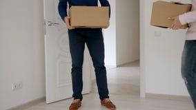 De vrouw met kleine doos gaat eerst bij witte heldere ruimte en de mens na haar binnen stock videobeelden