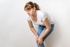De vrouw met kniepijn houdt haar pijnlijk been Royalty-vrije Stock Foto's