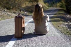 De vrouw met de kofferzitting op het asfalt wacht om de reis te hervatten door te liften Stock Foto's
