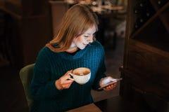 De vrouw met kop van koffie kijkt in smartphone en glimlacht in koffie stock afbeeldingen
