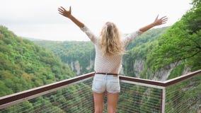 De vrouw met lang blond haar die zich met terug naar camera bevinden, die bergen bekijken, gelukkige dame spreidt wapens zoals vo stock videobeelden