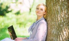 De vrouw met laptop het werk leunt in openlucht boom De notulen voor ontspannen Het meisjeswerk met laptop in park zit op gras On royalty-vrije stock foto