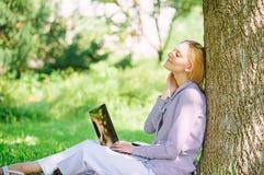 De vrouw met laptop het werk leunt in openlucht boom De notulen voor ontspannen Onderwijstechnologie en Internet-concept Het meis stock afbeeldingen