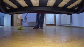 De vrouw met leren riemen wast de vloer onder het bed stock footage
