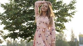 De vrouw met los eerlijk haar in roze kleding glimlacht en stelt stock videobeelden