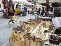 De vrouw met mand gaat heel wat manden voor verkoop op openluchtmarkt in Franse stad van briancon over Royalty-vrije Stock Foto