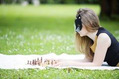 De vrouw met masker beslist bewegingsschaakstuk Stock Foto's