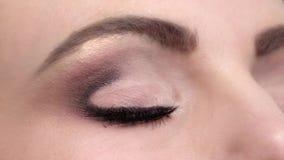 De vrouw met mooie blauwe ogen en de lange zwarte wimpers en helder maken, contactlenzen, omhoog sluiten, langzame motie stock footage