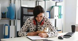 De vrouw met rode hoofdtelefoons op schouders het beduimelen boekt en het schrijven in potlood op papier stock video