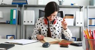 De vrouw met rode hoofdtelefoons op schouders het beduimelen boekt en het schrijven in potlood op papier stock footage
