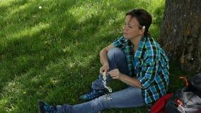 De vrouw met rugzakzitting onder de boom en omhult bloemen bekroont stock footage