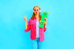 De vrouw met skateboard luistert aan muziek in draadloze hoofdtelefoons in een roze denimjasje royalty-vrije stock afbeelding