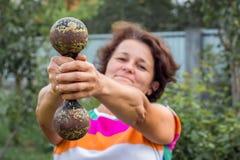 De vrouw met twee handen heft zware dumbbell_ op royalty-vrije stock afbeelding