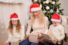De vrouw met twee kinderen opent de giften voor Nieuwjaarkerstmis Royalty-vrije Stock Foto