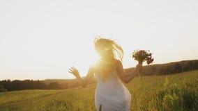 De vrouw met wild bloemboeket die op plattelandsgebied bij zonsondergang lopen, gelukkig meisje loopt in weide stock footage