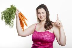 De vrouw met wortelen steunt wijsvinger Stock Fotografie