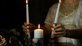 De vrouw in mooie kleren steekt kaarsen op een donkere achtergrond aan stock footage