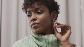 De vrouw in muntsweater in studio met grijze gordijnachtergrond, jaren '90 offise stijl stock video