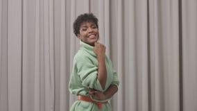 De vrouw in muntsweater in studio met grijze gordijnachtergrond, jaren '90 offise stijl stock footage