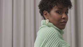 De vrouw in muntsweater in studio met grijze gordijnachtergrond, jaren '90 offise stijl stock videobeelden