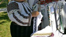 De vrouw naait met de hand Roemeense traditionele paterns op een canvas stock video