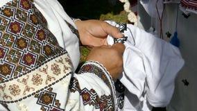 De vrouw naait met de hand Roemeense traditionele paterns op een canvas stock footage