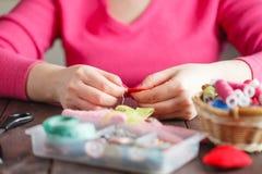 De vrouw naait rood hart gevormd stuk speelgoed door naald Stock Afbeelding