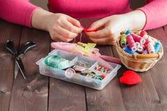 De vrouw naait rood hart gevormd stuk speelgoed door naald Stock Fotografie