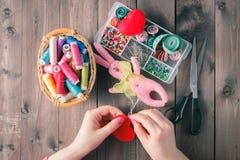 De vrouw naait rood hart gevormd stuk speelgoed door naald Stock Afbeeldingen