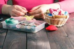 De vrouw naait rood hart gevormd stuk speelgoed door naald Royalty-vrije Stock Afbeeldingen