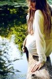 De vrouw in natte kleren en de natte haarzitting op een boom vertakken zich dichtbij stock afbeelding