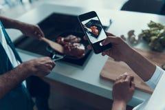 De vrouw neemt beelden op telefoon aangezien de mens vlees kookt stock afbeelding