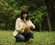 De vrouw neemt bladeren op Stock Afbeeldingen