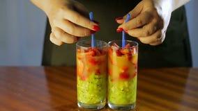 De vrouw neemt buisjes in glazen met een cocktail van kiwi en aardbeien op stock videobeelden