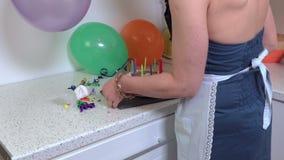 De vrouw neemt de cake van de verjaardagspartij en gaat vanaf keuken stock video
