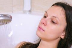 De vrouw neemt een bad Zij giet haar lichaamswater van de douche Het gezicht van de close-up royalty-vrije stock foto