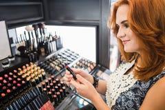 De vrouw neemt een lippenstift Stock Foto's