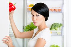 De vrouw neemt groene paprika van geopende koelkast Stock Foto's