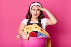 De vrouw neemt in handen reusachtig roze bassin met vuile kleren, dekens, handdoeken en andere huistextiel, treft voor was voorbe stock afbeeldingen