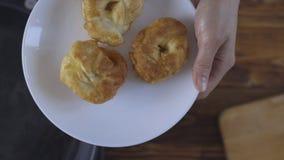 De vrouw neemt heet gebakje van pan stock videobeelden