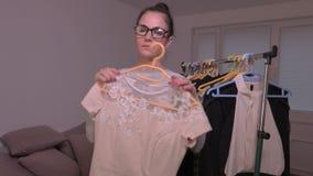De vrouw neemt kleding van het rek stock video